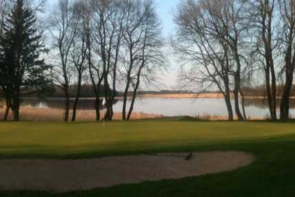 A view of a green with water in background at Waseca Lakeside Golf Club