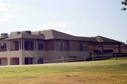 A view of a green and the clubhouse at Artesia Country Club