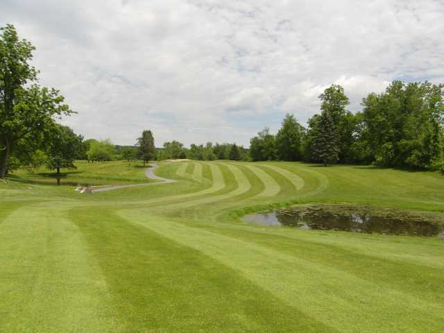 A view of a fairway with a pond on the right side at Lewistown Country Club