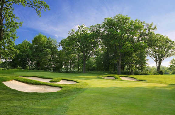 A view of a green guarded by bunkers at Cantigny Golf