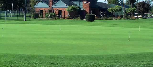 A view of the practice putting green with the clubhouse in background at Chandler Park Golf Course