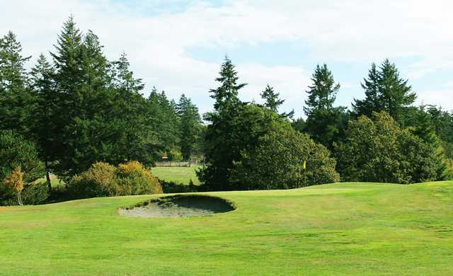 View of a green an bunker at Green Acres Golf Course