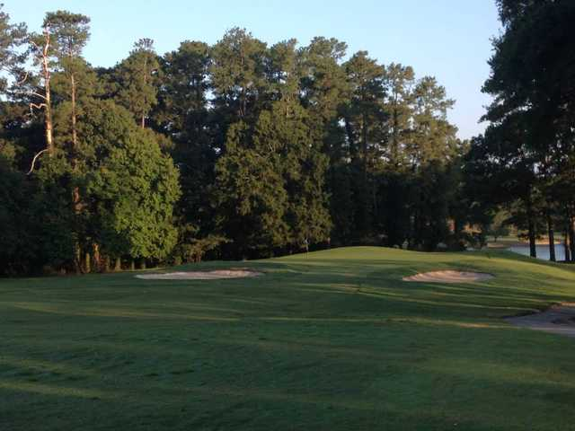 A view of a green protected by bunkers at Greenwood Country Club.