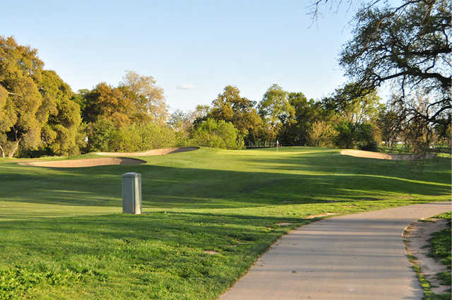 A view of a hole flanked by tricky sand traps at Haggin Oaks Golf Course