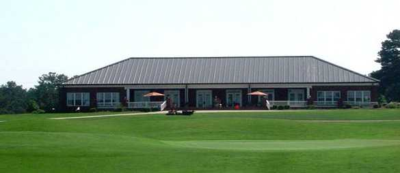 A view of a green with pro shop in background at Southern Hills Golf Club