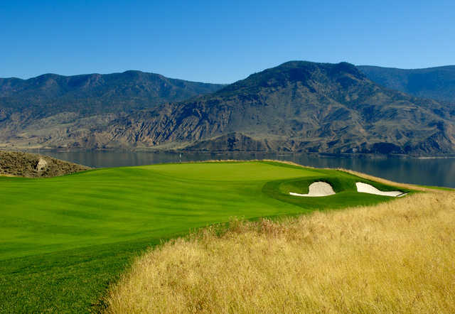 A view of a green with water in background at Tobiano Golf Course