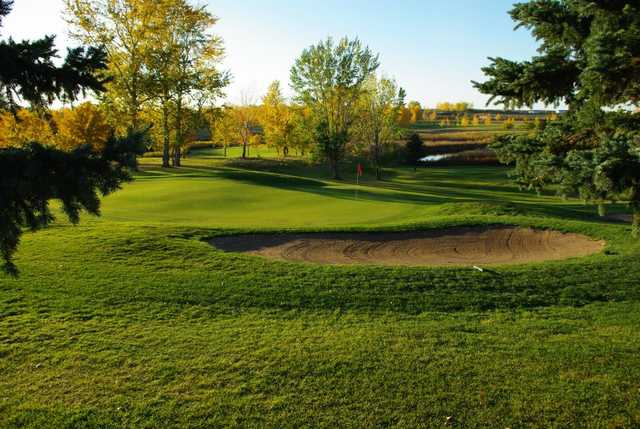 A view of a green protected by a bunker at Weyburn Golf Club