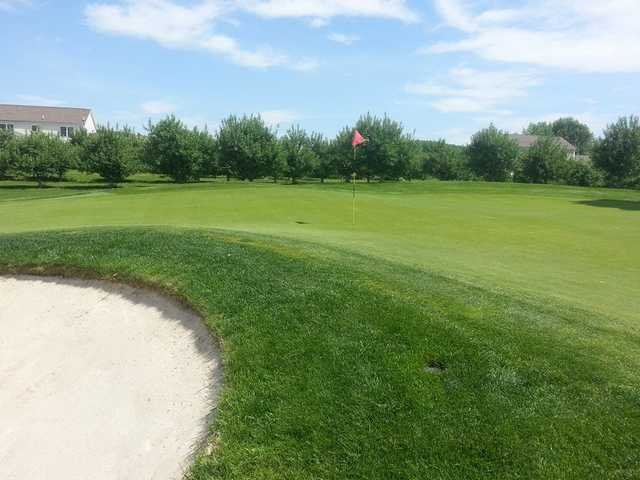A view of a hole guarded by a bunker at Apple Greens Golf Course