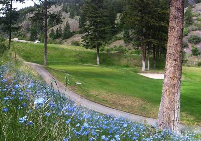 A view of a green protected by a bunker at Twin Lakes Golf Course