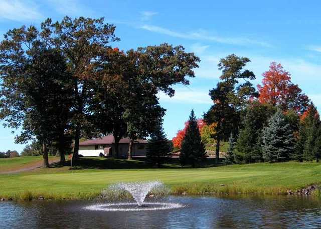 A view of a green with a water fountain in foreground at Luck Golf Course