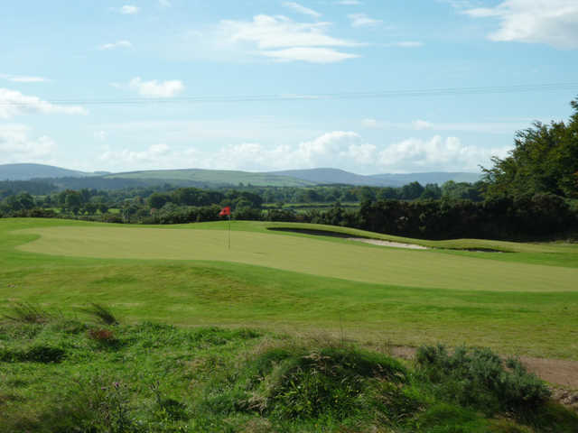 A view of a green protected by a bunker at Ballinastoe Golf Club