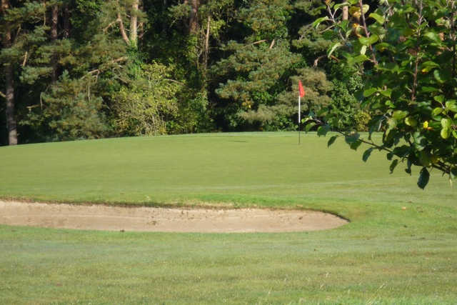 A view of a green protected by a sand trap at Loughgall Golf Club