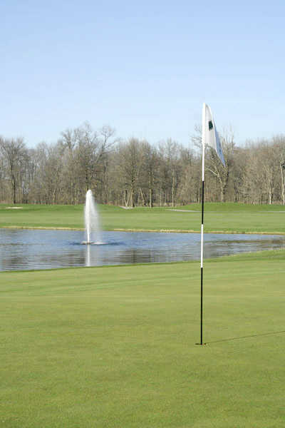 A view of the 14th hole at Bent Tree Golf Club surrounded by water