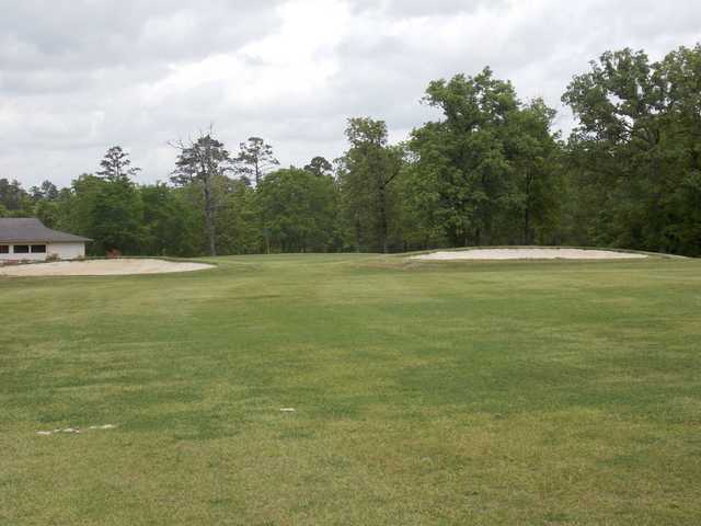 A view of a green flanked by bunkers at Neches Pines Golf Course