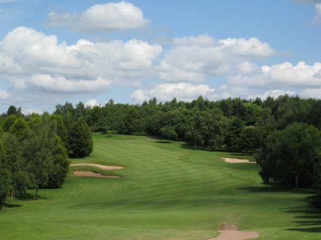 A view of the tree lined 10th green accompanied by several bunkers ant Bromsgrove Golf Course