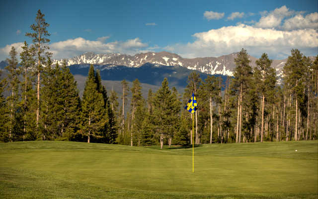 View of a green with mountains in the background from the Meadow Golf Course at Pole Creek Golf Club.