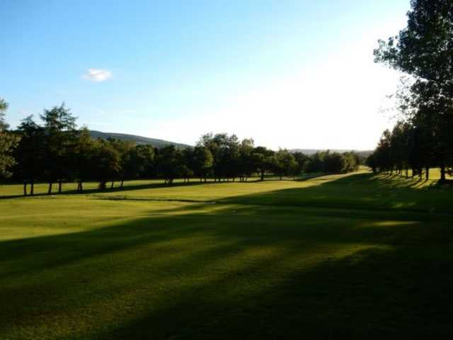 A scenic view of the fairway in the shadow of the trees at Glossop & District Golf Club