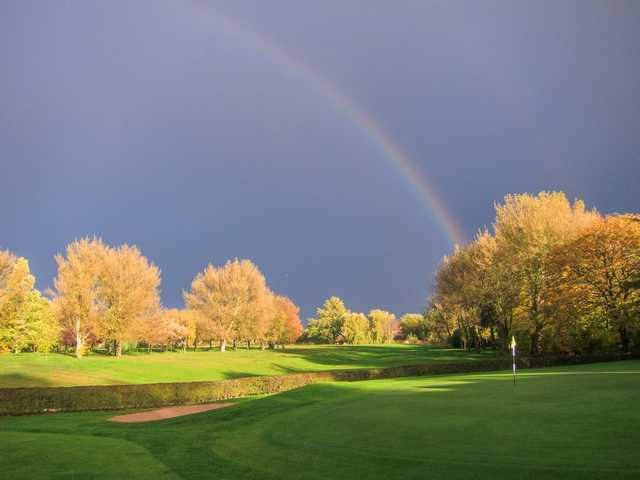 Beautiful shot of the 18th hole with a rainbow going over the course at  Heaton Moor Golf Club