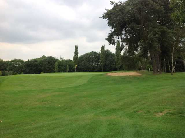 The 18th green and surrounding trees at Grims Dyke Golf Club
