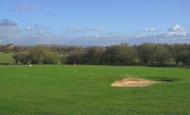 Scenic view of the short game area and surrounding trees at Great Lever and Farnworth Golf Club