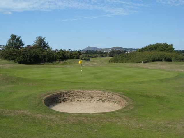 A view of the 11th green and surrounding mountains at Abersoch GC
