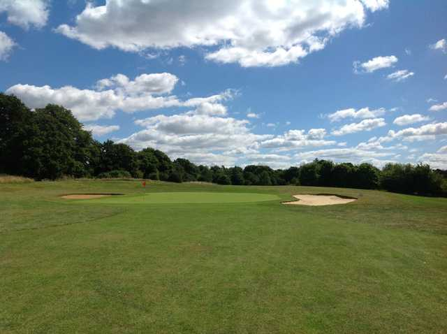 A view of teh 8th green and blue sky at Hurtmore Golf Club