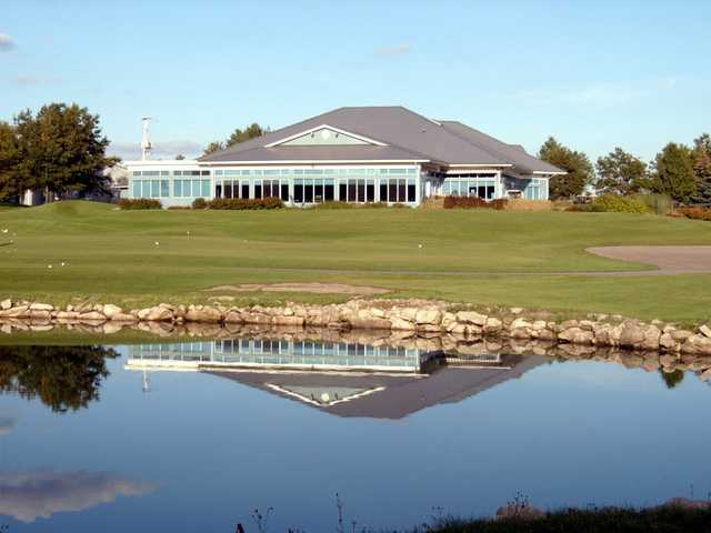 A view over the water of the practice area and the clubhouse at Carlisle Golf and Country Club