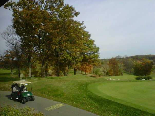 A fall view with golf cart in foreground from Mystic Creek Golf Club