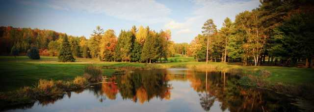 Fall view of a green over a pond at Pine Hills Golf Course