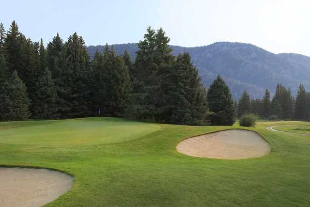 A view of a green protected by bunkers at Big Sky