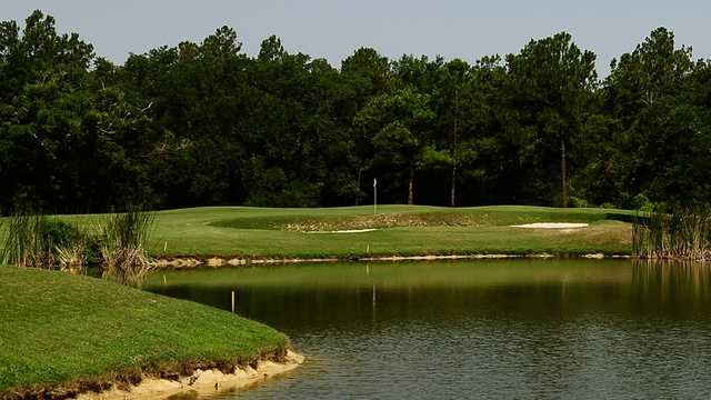 A view of the 12th hole surrounded by water at The Oaks Golf Club