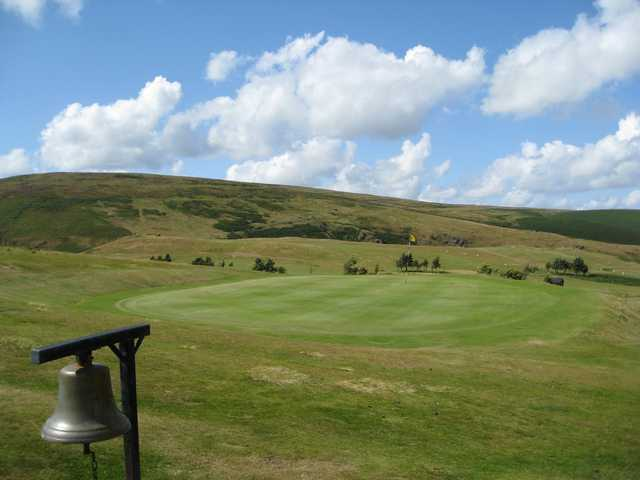 A View of the 14th green on a hilly backdrop at Church Stretton Golf Club