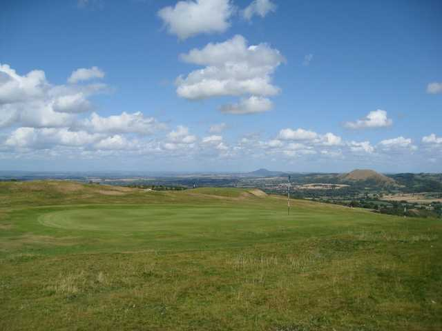 A picturesque view of the 9th green and hilly backdrop at Church Stretton Golf Club