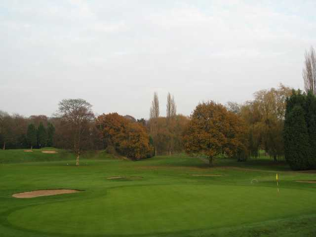 The challenging 9th green and greenside bunkers with surrounding trees at Withington Golf Club