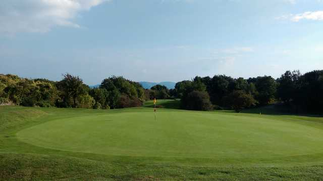 A view of the 3rd green and picturesque mountain backdrop at Llanymynech Golf Club