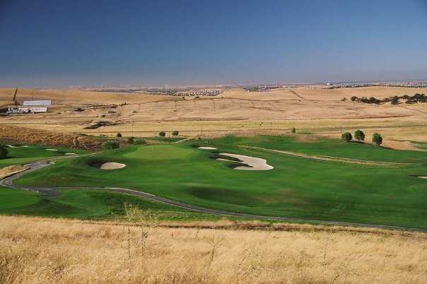 A view of the 1st green surrounded by sand traps at Roddy Ranch Golf Club