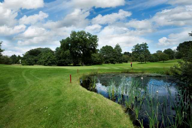 View across the pond of the 15th green at Tytherginton Golf Club