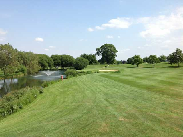 Scenic view of the 18th green and neighbouring pond at The Welcombe Golf Club