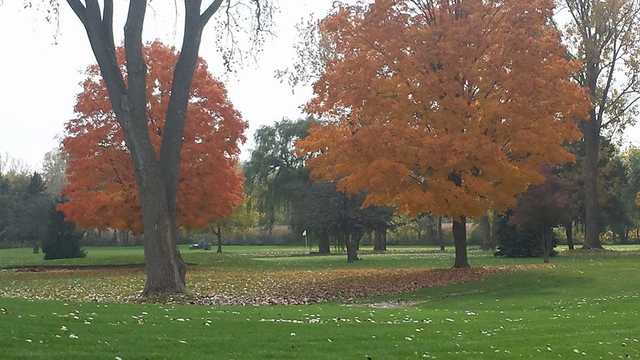 A view of a hole surrounded by trees with fall colors at Pond-A-River Golf Club