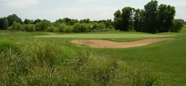 A view of a green protected by a bunker at Quail Ridge Golf Course
