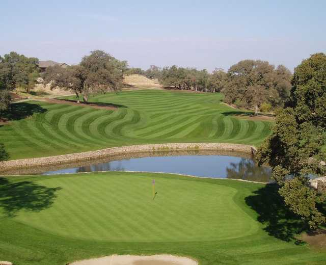 A view of a green with water in background at Catta Verdera Country Club