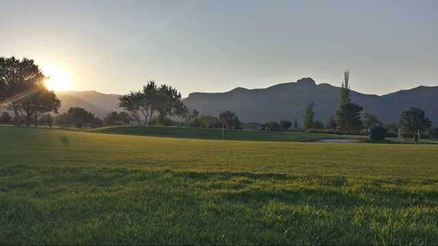 A sunny day view of a green at Desert Lakes Golf Course