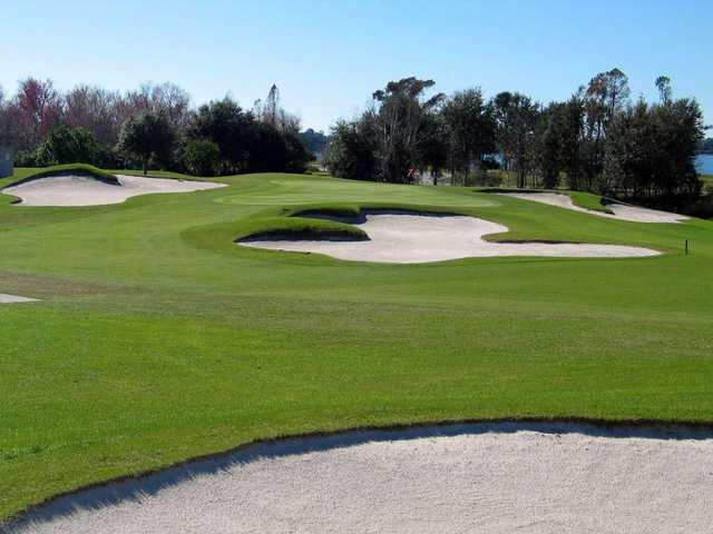 A view of a green surrounded by bunkers at Deer Island Country Club
