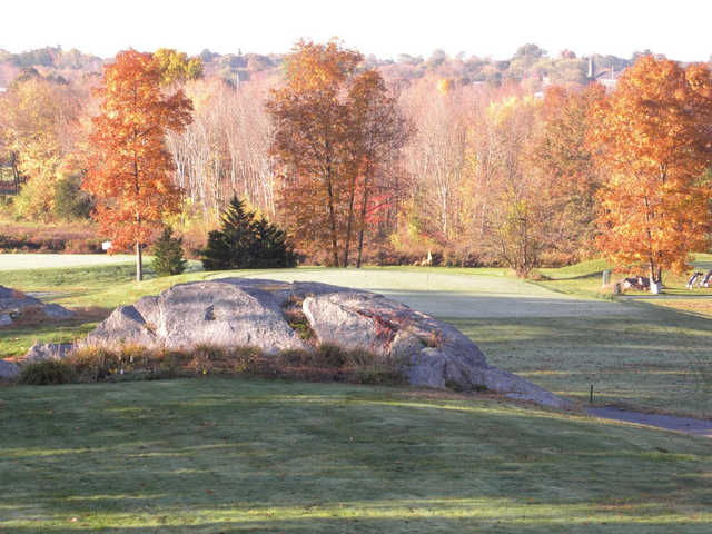 A view of a green surrounded by trees in fall colors at Windmill Hill Golf Course
