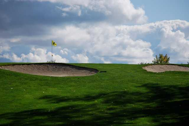 A view of a green protected by bunkers at Cedar Knoll Country Club