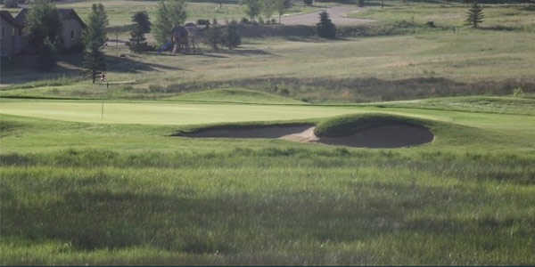 View of a green and bunker at King's Deer Golf Club