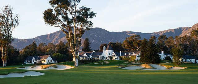 A view of a green flanked by sand traps and the clubhouse in background at Valley Club of Montecito