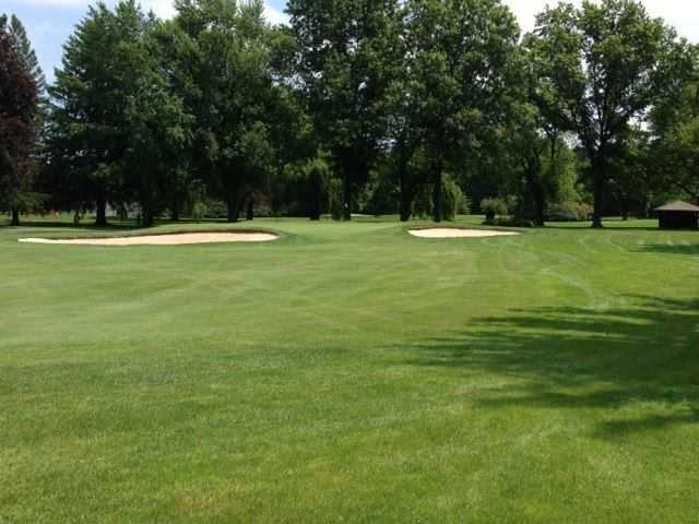 A view of a green flanked by bunkers at Madison Country Club