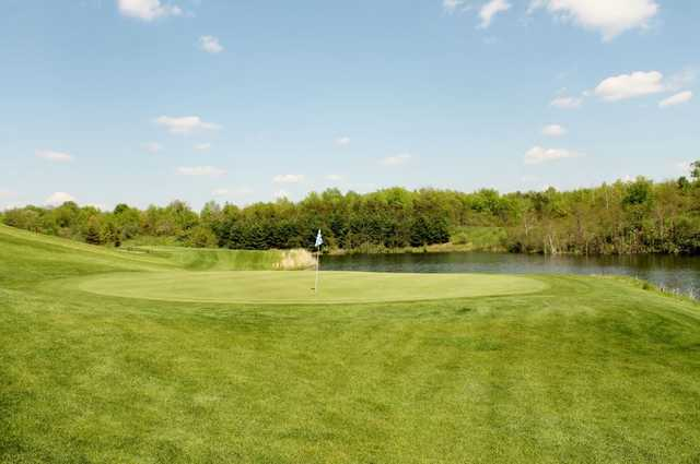 A view of a green with water in background at Reserve Run Golf Course