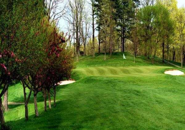 A view of a green protected by bunkers at Belmont Hills Country Club